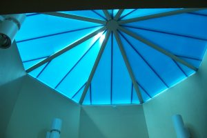 A polygon skylight from the interior, with green exterior panels to match the roof and a blue panels to to compliment the ceiling.
